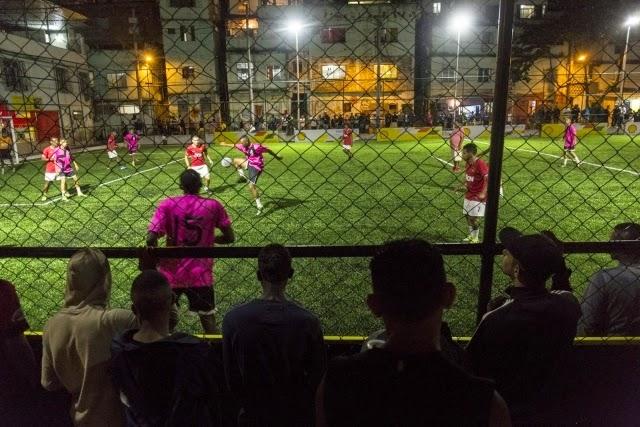 Le terrain de foot éclairé par les joueurs, la nuit